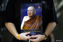 FILE - A man holds a portrait of Thailand's Supreme Patriarch, Somdet Phra Nyanasamvara Suvaddhana Mahathera, at Chulalongkorn Hospital in Bangkok, October 25, 2013.