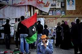 People look at photographs of people killed during the ongoing unrest in Benghazi, April 7, 2011
