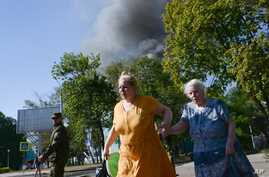 Women rush across the street after shelling in the town of Donetsk, eastern Ukraine, Wednesday, Aug. 27, 2014. The Obama administration accused Russia on Wednesday of orchestrating a new military campaign in Ukraine, helping rebel forces expand their...