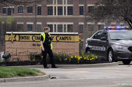 An Overland Park Kansas police officer guards the entrance to the scene of a shooting at the Jewish Community Center of Greater Kansas City in Overland Park, Kansas, April 13, 2014.