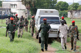 South Sudanese soldiers guard their colleagues, suspected of rape and murder, as they ride in a van before appearing in military in South Sudan's capital Juba, May 30, 2017.