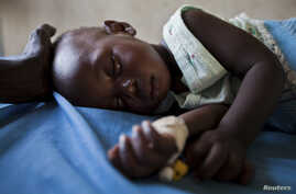 A young girl with malaria rests in the inpatient ward of the Malualkon Primary Health Care Center in Malualkon, in the South Sudanese state of Northern Bahr el-Ghazal, June 1, 2012.