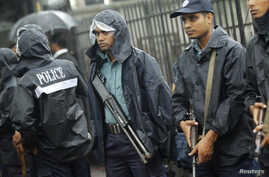 Police officers stand guard in front of the gate of International Crimes Tribunal (ICT) before a verdict against Bangladesh Jamaat-e-Islami chief Motiur Rahman Nizami in Dhaka, June 24, 2014. The ICT postponed the verdict due to his illness, local me