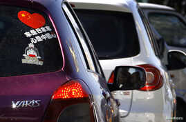 A Toyota car with a sticker attached to the rear window reading 'Japanese car, Chinese heart' is seen along a main road in central Beijing, October 9, 2012.