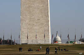 People walk near the Washington Monument, with the U.S. Capitol in the background, Dec. 26, 2018, as the partial government shutdown continues in Washington. A shutdown affecting parts of the federal government threatens to carry over into January.