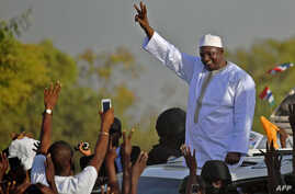 Gambia's new president Adama Barrow waves to supporters as he leaves the airport in Banjul, Jan. 26, 2017, after returning from Senegal.