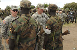 In this Wednesday, April 20, 2011 file photo, U.S. Army soldiers are seen with Uganda People's Defence Force soldiers at the closing ceremony for operation ATLAS DROP 11, an annual joint aerial delivery exercise, in Soroti, Uganda. While putting few