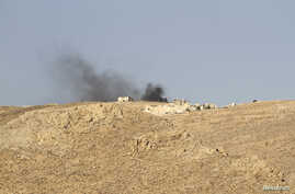 Smoke rises from a Lebanese army base as Lebanese Army soldiers clash with Islamist militants on the mountains next to the entrance of Arsal, August 3, 2014.