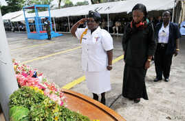 FILE - Liberian Minister of Justice Christine Tah (center right) observes a moment of silence with a senior female police officer at a 2011 ceremony for  fallen peacekeepers.