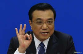 China's Premier Li Keqiang gestures as he speaks during a news conference, after the closing ceremony of the Chinese National People's Congress (NPC) at the Great Hall of the People, in Beijing, March 13, 2014.