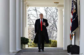 FILE - President Donald Trump waves as he walks through the Colonnade from the Oval Office of the White House, Jan. 25, 2019.
