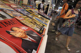 FILE - A copy of Time Magazine featuring portraits of Chinese leader Xi Jinping and former leader Mao Zedong on its cover is seen on display at an annual book fair in Hong Kong, July 20, 2016.