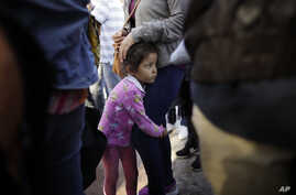 In this June 13, 2018 photo, Nicole Hernandez, of the Mexican state of Guerrero, holds on to her mother as they wait with other families to request political asylum in the United States, across the border in Tijuana, Mexico.