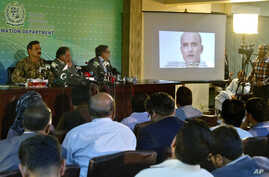 FILE - Journalists look at a photo of Indian national Kulbhushan Jadhav during a press conference in Islamabad, Pakistan, March 29, 2016.