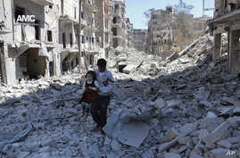 FILE - A Syrian man holds a girl as he stands on the rubble of houses that were destroyed by Syrian government forces air strikes in Aleppo, Syria, on April 21, 2014. The French foreign minister says Russia could face war crimes for its bombing camp