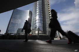 FILE - People walk in the Porta Nuova business center in Milan, Italy, March 11, 2016.