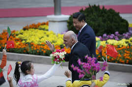 Afghanistan's President Ashraf Ghani Ahmadzai (L) waves to students as he and China's President Xi Jinping attend a welcoming ceremony outside the Great Hall of the People, in Beijing, Oct. 28, 2014.