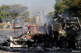 Locals walk past a shell of a burnt out truck used to barricade roads by protesters in Atteridgeville, a township west of Pretoria, South Africa, June 21, 2016.