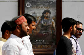 "People walk past a poster of an Indian movie ""Baahubali: The Beginning"" outside a movie theater in New Delhi, India, April 12, 2017."