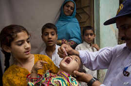 A Pakistani health worker gives a polio vaccine to a child in Rawalpindi, Pakistan, on May 6, 2014.