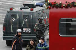 People walk past an armed Chinese paramilitary policeman standing guard in the capital city's popular shopping and nightlife area of Sanlitun in Beijing, Dec. 27, 2015.
