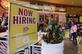FILE - a restaurant posts a sign indicating they are hiring, in Miami.