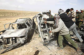Rebel fighters push cars burnt in what they say was a coalition airstrike on a group of vehicles killing around ten on the road between Ajdabiyah and Brega, in Libya, April 2, 2011