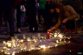 Brussels residents gather at the Bourse to light candles in memory of those killed in the terror attacks and sing songs of solidarity, March 22, 2016. (L. Bryant/VOA)