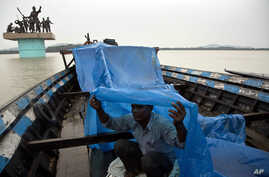An Indian boatman uses a plastic sheet to protect himself from the rain, on the river Brahmaputra in Gauhati, India, May 30, 2017. Several northeastern Indian states experienced heavy rainfall as an effect of tropical Cyclone Mora that lashed souther