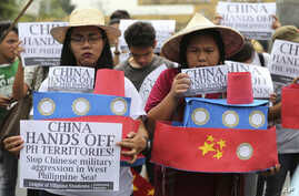 Filipino student activists hold mock Chinese ships to protest recent island-building and alleged militarization by China off the disputed Spratlys group of islands in the South China Sea during a rally near the Malacanang presidential palace in Manil