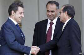 French President Nicolas Sarkozy, left, shakes hands with Mahmoud Jibril, right, and Ali Al-Esawi, representatives of the newly formed council based in the eastern Libyan city of Benghazi, after a meeting at the Elysee Palace, in Paris, March 10, 201
