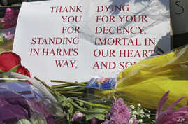 A sign of thanks rests against a traffic light pole at a memorial outside the transit center in Portland, Ore., May 27, 2017. People stopped with flowers, candles, signs and painted rocks for two bystanders who were stabbed to death Friday while tryi...