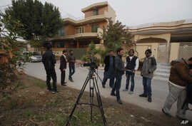 Pakistani journalists and local residents gather out the home of Salman Haider, a university professor and rights activists, following news of his return, in Islamabad, Pakistan, Jan, 28, 2017.