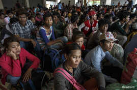 Cambodian workers wait for their documents to be processed at the Aranyaprathet police station as they prepare to move back to Cambodia in Sa Kaew, Thailand, June 15, 2014.
