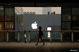 A woman walks past an Apple store in Beijing, China, July 28, 2016.