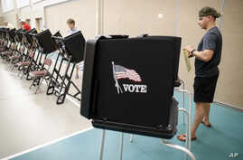 Voters cast their ballots in a polling station at Quest Community Church, Aug. 7, 2018, in Westerville, Ohio.