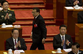 Chinese Premier Li Keqiang, center walks past Chinese President Xi Jinping, at right to deliver a work report for the opening session of the annual National People's Congress in Beijing's Great Hall of the People, March 5, 2016.