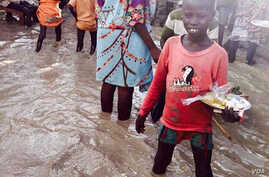 A child stands in floodwaters at a camp for people displaced by violence, Bentiu, South Sudan (G. Joselow/VOA).