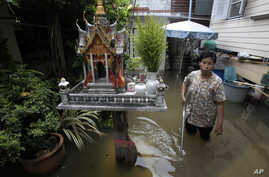 FILE - A Thai resident wades through a flooded area in Bangkok, Thailand, Oct.  3, 2011. Floods account for most of all disaster-related funding.