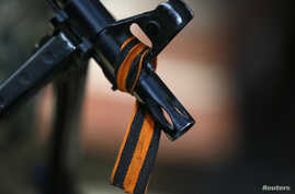 FILE - The black and orange ribbon of St. George, a symbol widely associated with pro-Russian protests in Ukraine, is tied to the machine gun of a pro-Russian armed man in Slaviansk, Kazakhstan, April 21, 2014.