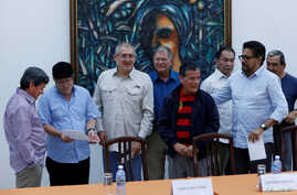 Revolutionary Armed Forces of Colombia (FARC) commander, Timoleon Jimenez (2nd L), talks to Pablo Beltran, (L) representative of Colombian National Liberation Army (ELN) during a joint news conference in Havana, Cuba, May 11, 2017.