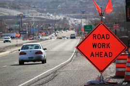 FILE - Construction signs warn drivers on US Route 550 as crews prepare to begin work on the highway in Bernalillo, N.M., Feb. 19, 2015.