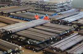 Workers check steel products at a factory in Dalian, Liaoning Province, China, March 30, 2016.