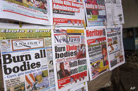 A close - up of newspaper front pages focusing on the Ebola outbreak, including a newspaper, reading 'Burn all bodies' in Monrovia, Liberia, July 31, 2014.