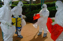 FILE - Officials from the World Health Organization wear protective clothing on July 28, 2012 as they prepare to enter Kagadi Hospital in Kibale District, about 200 kilometres from Kampala.