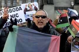 Libyans living in Prague, Czech Republic hold banners and Libya's old national flags as they shout slogans during a protest against the Libyan leader Moammar Gadhafi and condemned the bloody crackdown on the protesters, February 25, 2011