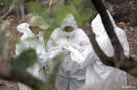 Forensic technicians check charred bones found at a site believed to be a mass grave at an abandoned ranch in the municipality of Garcia, on the outskirts of Monterrey, Mexico, May 31, 2017. Fourteen bodies were found this week in a mass grave near t