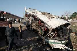 Afghans and security forces inspect damage to a bus after a suicide attack in Jalalabad east of Kabul, Afghanistan, April 11, 2016.