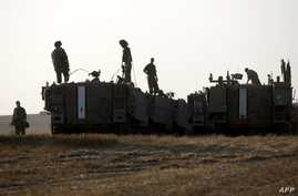 Israeli soldiers stand on their armoured personnel carrier (APC)  in an army deployment area near the border with the Gaza Strip, July 6, 2014.