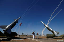 FILE - People watch S-300 air defense missile systems launching missiles during the Keys to the Sky competition at the International Army Games 2017 at the Ashuluk shooting range outside Astrakhan, Aug. 5, 2017.